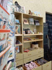 Palanderin talon museokauppa. Etualalla postikortteja, taustalla hylly, jossa muita myyntituotteita