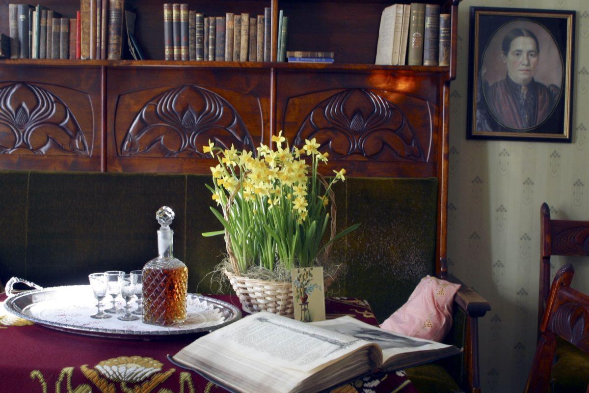 Kuvituskuva Palanderin talon herrainhuoneen pöydällä on narsisseja ruukussa, konjakkipullo sekä lasit hopeatarjottimella sekä avonainen raamattu.
