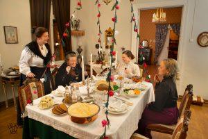 Palanderin talon saliin on katettu joulupöytä. Pöydän ympärillä Palanderin talon asukkaita ja palvelusväkeä.