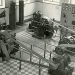 Mustavalkoinen valokuva Ahveniston vesilaitoksesta sisältä. Kuvassa ruudullinen laattalattia sekä vesipumppujen moottoreita.