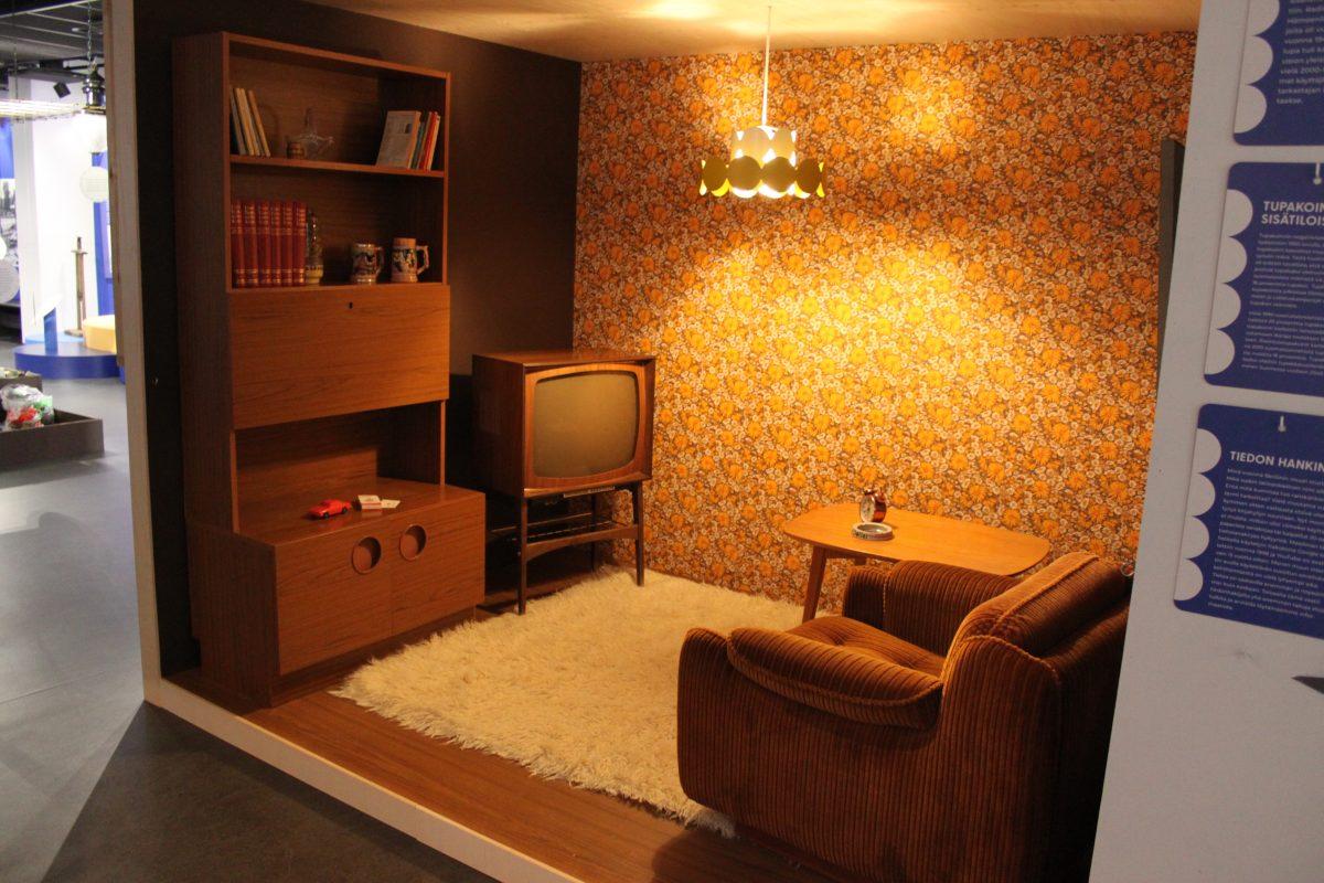 Valokuva Ennen kaikki ei ollut paremmin -näyttelystä. Kuvassa on olohuone 1970-luvulta ruskeasävyisine kalusteineen ja tapetteineen.