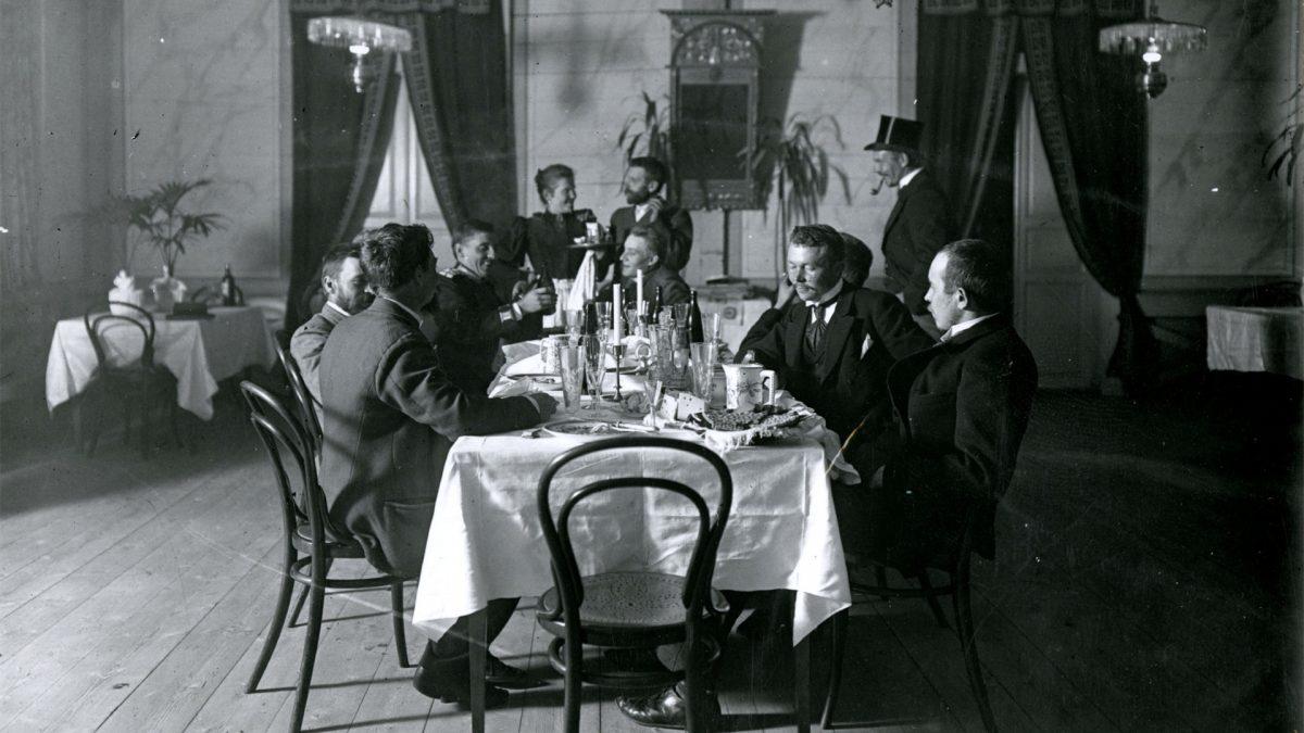 Mustavalkoinen kuva pöytäseurueesta hämeenlinnalaisessa Puistoravintolassa noin vuonna 1900.