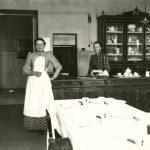 Mustavalkoinen kuva, jonka etualalla pöydälle on katettu valkoisen liinan päälle astiat. Taustalla henkilö seisoo tiskin edessä mekossa ja valkoisessa esiliinassa. Tiskin takana seisoo toinen henkilö tummassa puvussa.