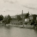 Mustavalkoisessa valokuvassa etualalla vettä, kivestä rakennetut rannat, vasemmalla rannassa asuinrakennus, oikella vaalea suuri ja arvokkaan näköinen asuinrakennus. Taustalla tehdasrakennuksia ja savupiippu.
