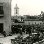 Mustavalkoinen valokuva, jossa ihmisiä ja hevoskärryjä seisoo sankoin joukoin Anniskeluyhtiön talon edessä.