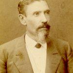 Mustavalkoinen, kellastunut valokuva miehestä, jolla on viikset, pujoparta, tummatakki, liivi, valkoinen kauluspaita ja solmuke kaulassa.