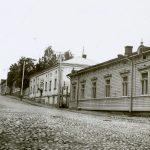 Mustavalkoinen valokuva otettu ylämäkeä kohti. Katu on mukulakiveystä ja oikealla puolella kuvassa on kaksi vaaleaa matalaa rakennusta, jotka näyttävät asuintaloilta. Toinen rakennuksista on puutalo ja toinen kivitalo.