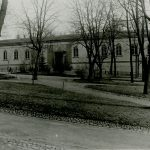 Mustavalkoisessa valokuvassa etualalla lehdettömiä puita ja niiden takana vaalea pitkä matala rakennus.