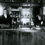 Mustavalkoinen valokuva, jossa baaritiskin takana seisovat mies ja nainen. Heidän takanaan avohyllyllä on alkoholipulloja.