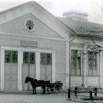 Kuvassa vaalea korkea rakennus, jossa kolmet pariovet. Pariovien edessä seisoo hevonen rattaineen.